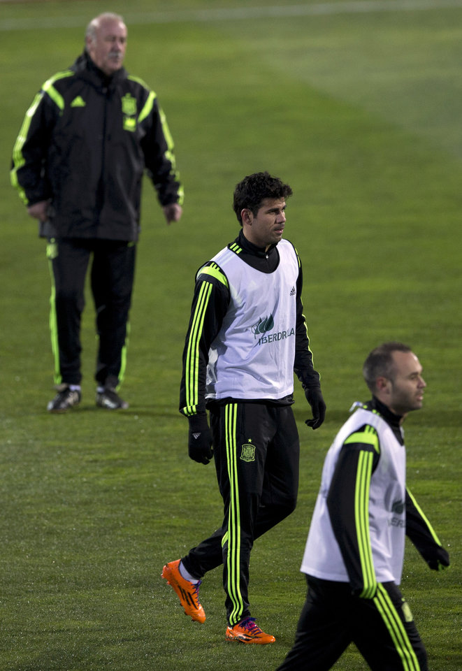 Photo - Spain's  coach Vicente del Bosque, top watches Diego Costa, centre and Andres Iniesta during a training session in Madrid, Monday March 3, 2014. Spain will play Italy Wednesday in a friendly soccer match. (AP Photo/Paul White)