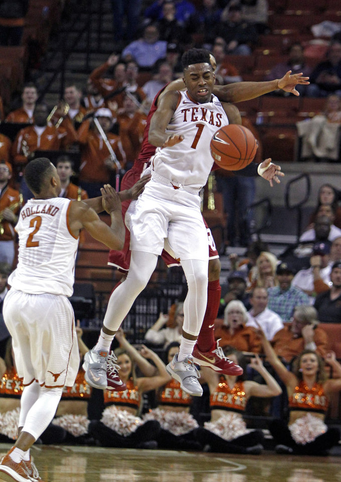 Photo - Texas guard Isaiah Taylor (1) goes for the loose ball against Oklahoma guard Isaiah Cousins during the second half an NCAA college basketball game, Monday, Jan. 5, 2015, in Austin, Texas. Oklahoma won 70-49.  (AP Photo/Michael Thomas)