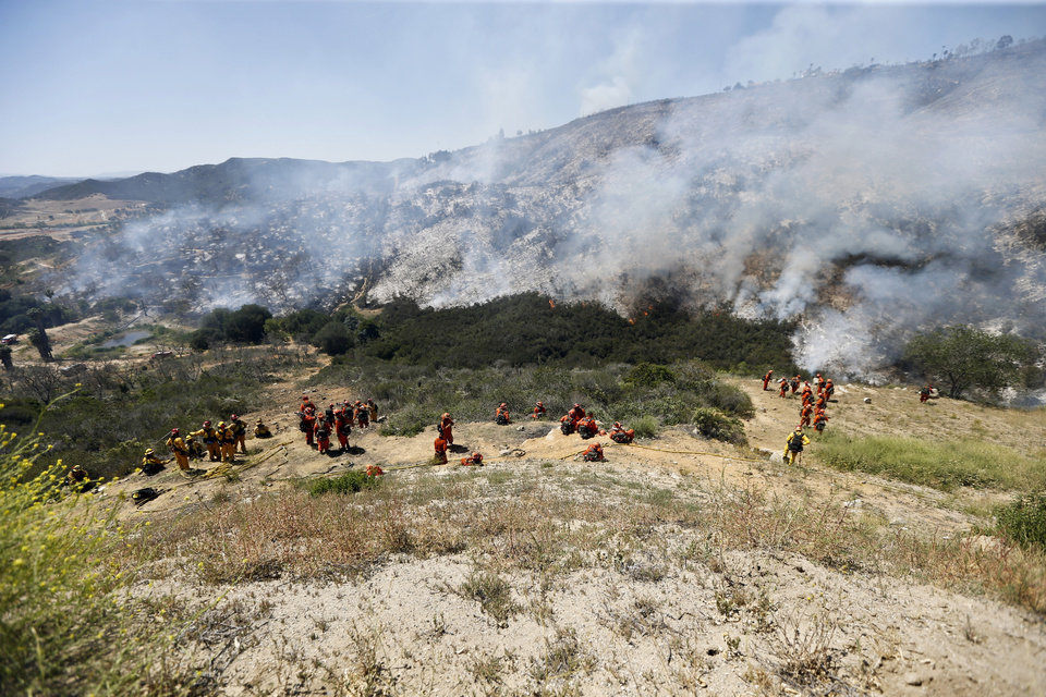 Photo - Firefighters move back down the embankment to the brush fire Thursday, May 15, 2014, in San Marcos, Calif. Gusty winds failed to return Thursday morning in San Diego County wildfire areas and authorities said it was a window of opportunity to make further gains against flames that burned homes and drove tens of thousands from their homes. (AP Photo)