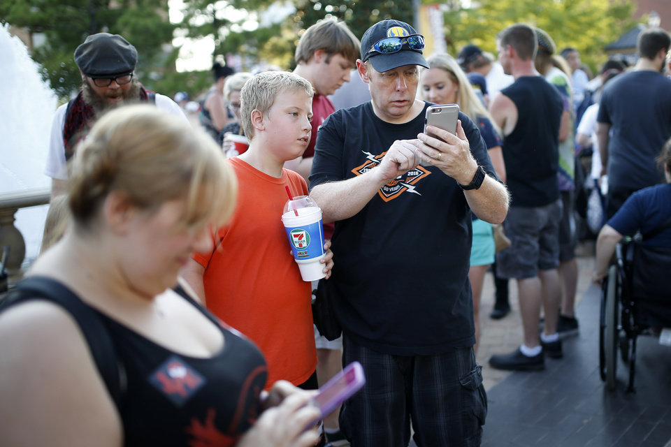 Photo - Michael Cross and his son Aidyn Cross, 10, of Oklahoma City play Pokemon Go during a meetup for players of the game in Oklahoma City at Bricktown on Friday, July 29, 2016. Photo by Bryan Terry, The Oklahoman