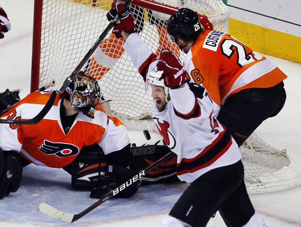 Photo -   Philadelphia Flyers goalie Ilya Bryzgalov, left, and defenseman Erik Gustafsson, right, look at the puck in the net as New Jersey Devils' Travis Zajac, center, shouts after he scored the Devils third goal during the third period in Game 2 of an NHL hockey Stanley Cup second-round playoff series with the Philadelphia Flyers, Tuesday, May 1, 2012, in Philadelphia. The Devils won 4-1 evening the best of seven series at 1-1.(AP Photo/Tom Mihalek)