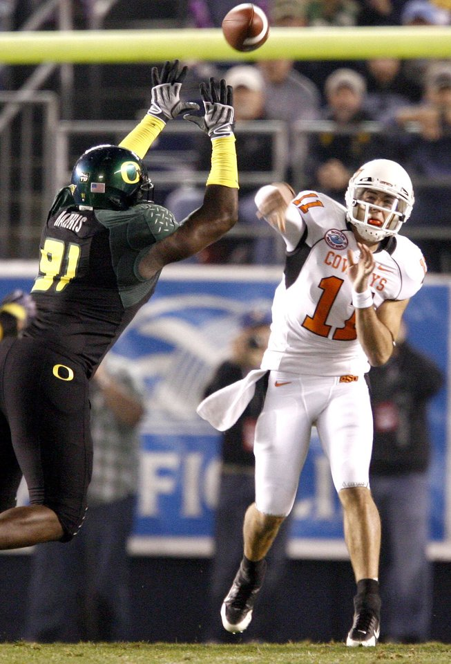 Photo - OSU's Zac Robinson passes the ball past Oregon's Ra'Shon Harris during the Holiday Bowl college football between Oklahoma State and Oregon at Qualcomm Stadium in San Diego, Tuesday, Dec. 30, 2008.  PHOTO BY BRYAN TERRY, THE OKLAHOMAN.