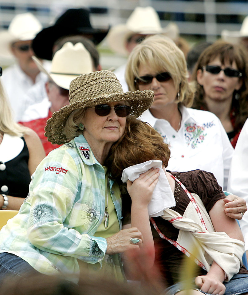 Photo - Sharon Shoulders (left) comforts her grandaughter Ellie during funeral services for Jim Shoulders in Henryetta, Okla., on Sunday,  June 24, 2007. By John Clanton, The Oklahoman