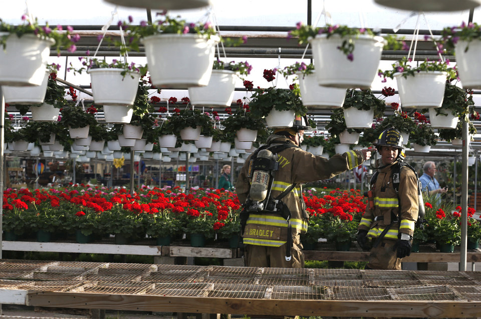 Photo - Firefighters clean up from a fire at TLC Florists and Greenhouses, located at 105 W. Memorial Rd., near Memorial and Santa Fe in Oklahoma City, Friday, Feb. 21, 2014. Photo by Sarah Phipps, The Oklahoman