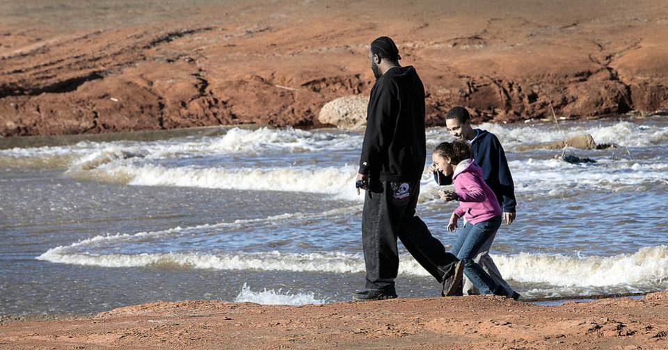 Photo - Derrick Wiggins and his children, Katija, 9, and Dalin, 12, watch water from Canton Lake flow Monday into Lake Hefner in Oklahoma City.  Photo By David McDaniel, The Oklahoman
