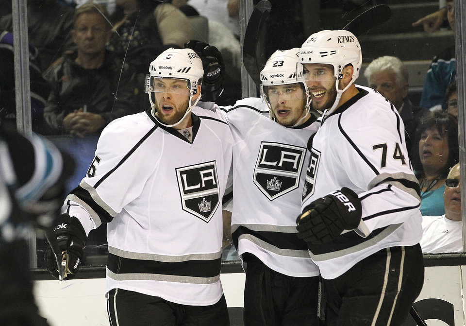 Los Angeles Kings right wing Dustin Brown, center, celebrates with teammates defenseman Jake Muzzin (6) and center Dwight King (74) after scoring a goal against the San Jose Sharks during the second period in Game 6 of their second-round NHL hockey Stanley Cup playoff series in San Jose, Calif., Sunday, May 26, 2013. (AP Photo/Tony Avelar)