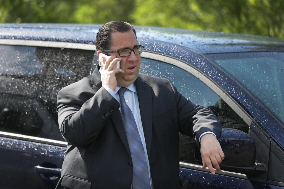 Attorney David Chasnick talks on a phone near the scene in Oakland Township, Mich., Monday, June 17, 2013 where officials search for the remains of Teamsters union president Jimmy Hoffa who disappeared from a Detroit-area restaurant in 1975. Chasnick represents reputed Mafia captain Tony Zerilli who told Detroit TV station WDIV that he knew where Hoffa was buried and that the FBI had enough information for a search warrant to dig at the site. (AP Photo/Carlos Osorio)