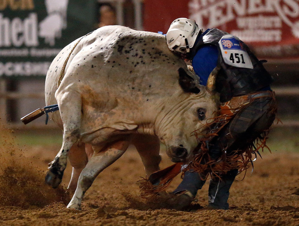 Taylor Broussard tries to get loose from a bull during the International Finals Youth Rodeo in Shawnee, Okla., Sunday, July 8, 2012. Photo by Sarah Phipps, The Oklahoman