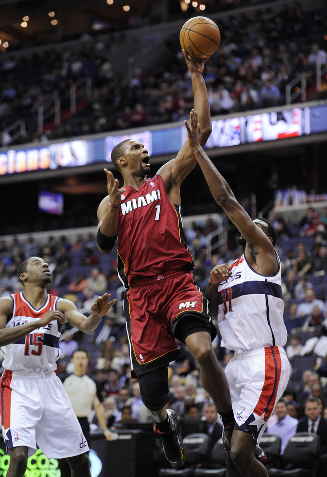 Photo - Miami Heat center Chris Bosh (1) goes to the basket against Washington Wizards' Chris Singleton (31) and Jordan Crawford (15) during the first half of an NBA basketball game, Tuesday, Dec. 4, 2012, in Washington. (AP Photo/Nick Wass)