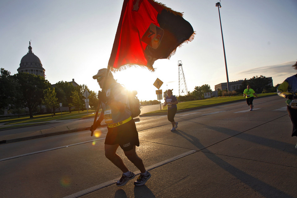 Photo - Rick Wagner carries a flag as he runs down Lincoln Boulevard during the tenth anniversary of the 2010 Oklahoma City Memorial Marathon on Sunday, April 25, 2010, in Oklahoma City, Okla.   Photo by Chris Landsberger, The Oklahoman  ORG XMIT: KOD