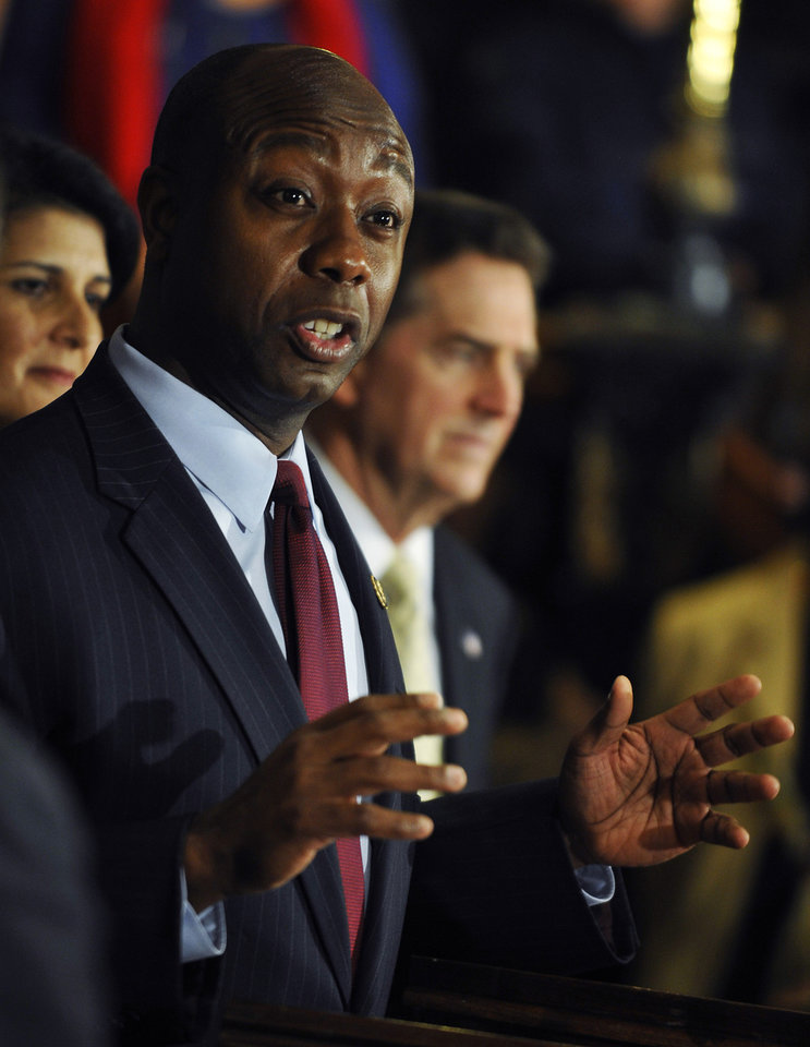 U.S. Rep. Tim Scott speaks during a news conference after being named Jim DeMint's replacement in the U.S. Senate at the South Carolina Statehouse on Monday, Dec. 17, 2012, in Columbia, S.C. At rear, are South Carolina Gov. Nikki Haley, left, and Sen. Jim DeMint. (AP Photo/Rainier Ehrhardt)