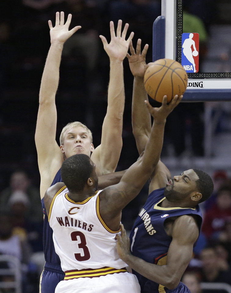 Photo - New Orleans Pelicans' Greg Stiemsma, left, and Tyreke Evans, right, block a shot by Cleveland Cavaliers' Dion Waiters (3) during the first quarter of an NBA basketball game, Tuesday, Jan. 28, 2014, in Cleveland. (AP Photo/Tony Dejak)