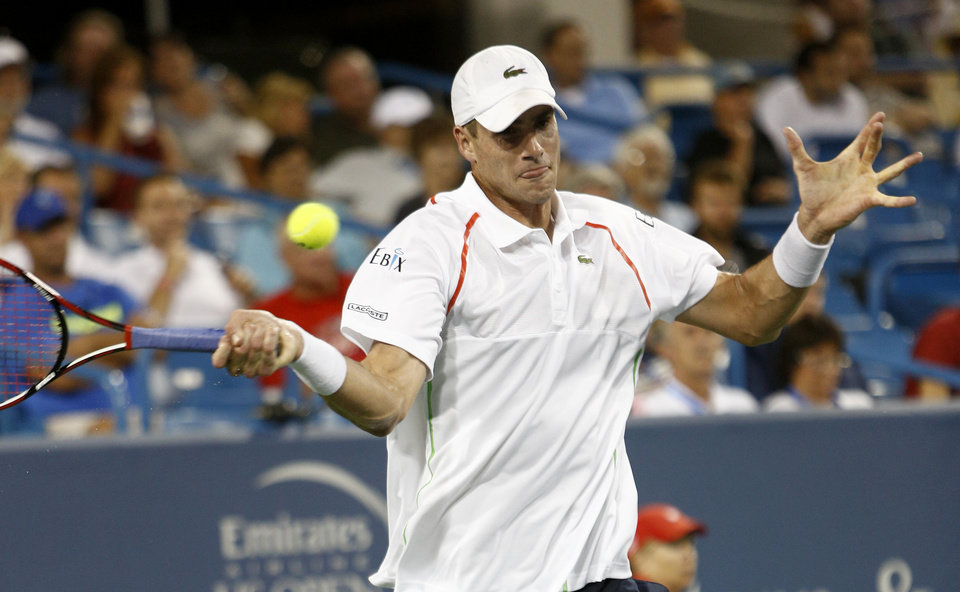 Photo - John Isner, from the United States, returns a volley to Kevin Anderson, from South Africa, in a first round match at the Western & Southern Open tennis tournament, Monday, Aug. 11, 2014, in Mason, Ohio. Isner won 6-3, 6-4. (AP Photo/David Kohl)