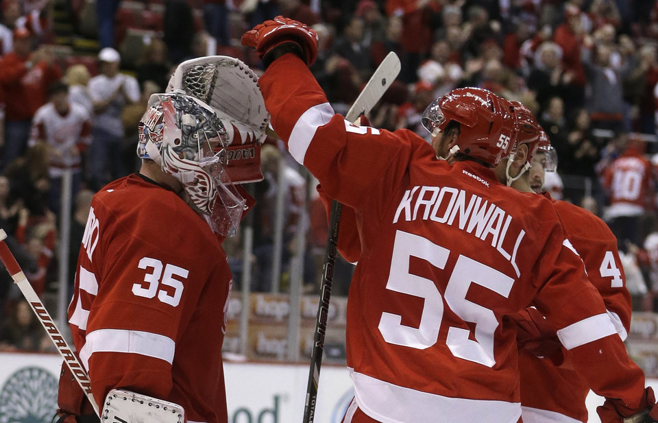 Photo - Detroit Red Wings goalie Jimmy Howard (35) is congratulated by defenseman Niklas Kronwall (55) of Sweden after their 2-0 win over the Vancouver Canucks in an NHL hockey game in Detroit, Monday, Feb. 3, 2014. (AP Photo/Carlos Osorio)