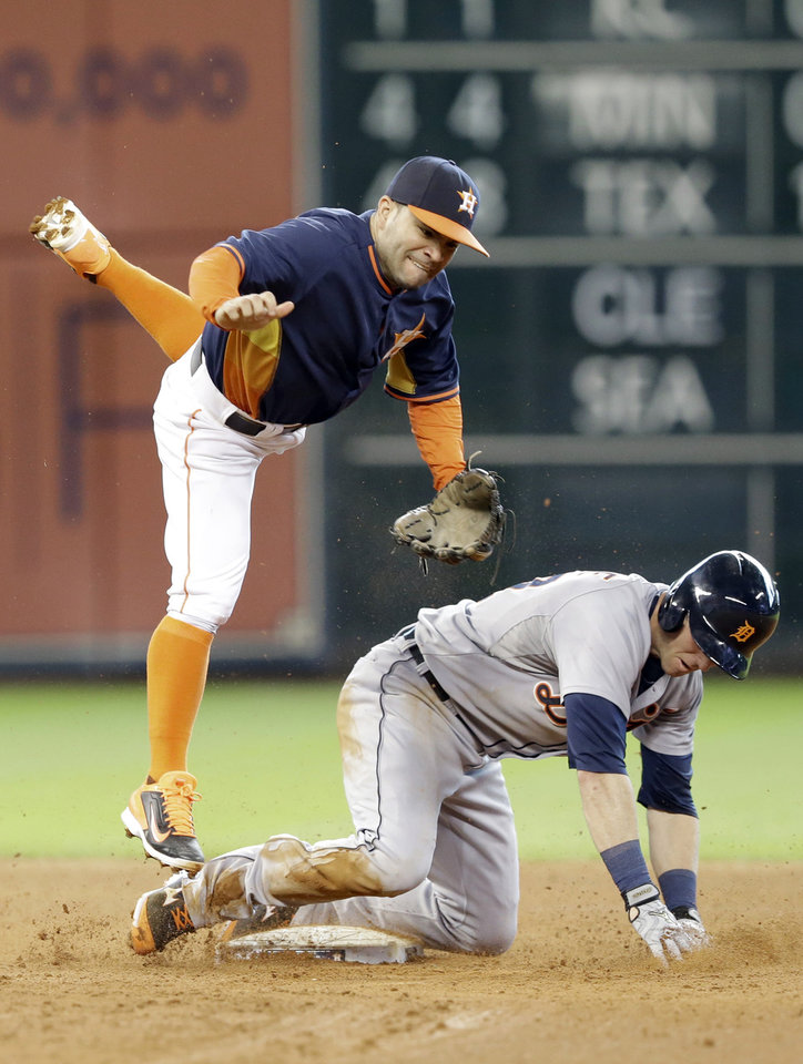 Photo - Houston Astros second baseman Jose Altuve, left, tries to keep from landing on Detroit Tigers' Andrew Romine after turning the double play on Austin Jackson in the fifth inning of a baseball game Sunday, June 29, 2014, in Houston. (AP Photo/Pat Sullivan)