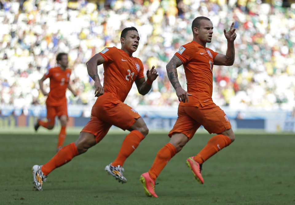 Photo - Netherlands' Wesley Sneijder, right, celebrates after scoring his side's first goal during the World Cup round of 16 soccer match between the Netherlands and Mexico at the Arena Castelao in Fortaleza, Brazil, Sunday, June 29, 2014. (AP Photo/Natacha Pisarenko)