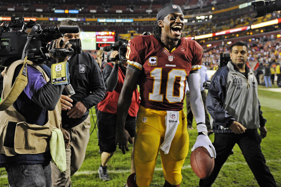Photo - Washington Redskins quarterback Robert Griffin III celebrates as he leaves the field after an NFL football game against the New York Giants in Landover, Md., Monday, Dec. 3, 2012. The Redskins won 17-16. (AP Photo/Nick Wass)