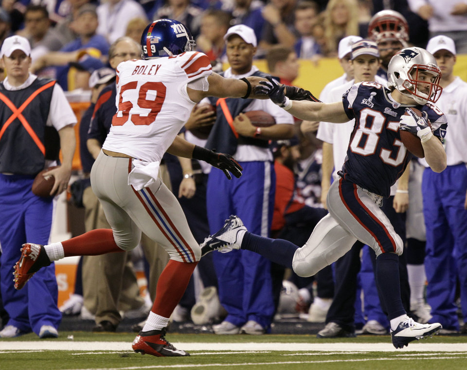 Photo - New England Patriots wide receiver Wes Welker (83) runs from New York Giants linebacker Michael Boley, left, during the first half of the NFL Super Bowl XLVI football game, Sunday, Feb. 5, 2012, in Indianapolis. (AP Photo/Marcio Jose Sanchez) ORG XMIT: SB242