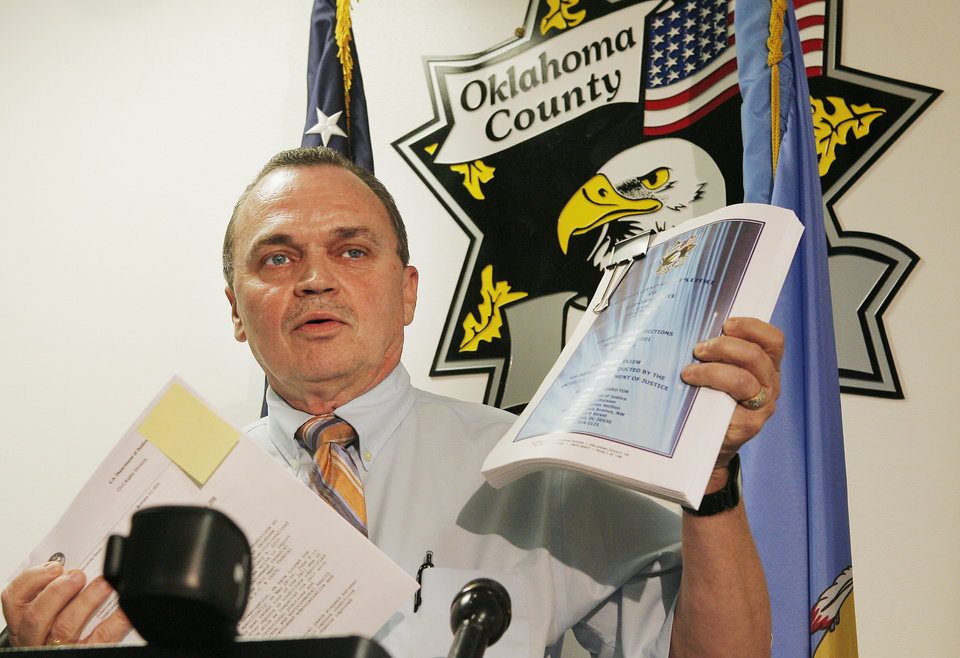 Photo - OKLAHOMA COUNTY JAIL: Sheriff John Whetsel holds up the a 148 page report from the Department of Justice and a copy of their response at a press conference, Monday, August 4, 2008.    Photo by David McDaniel, The Oklahoman  ORG XMIT: KOD