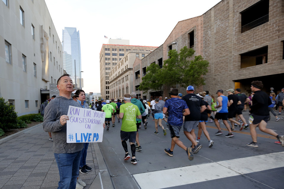 Photo - Kevin Parkerson of Bentonville, Ark., holds a sign as he watches for his daughter Abby Parkerson during the Oklahoma City Memorial Marathon in Oklahoma City, Sunday, April 28, 2019. [Bryan Terry/The Oklahoman]