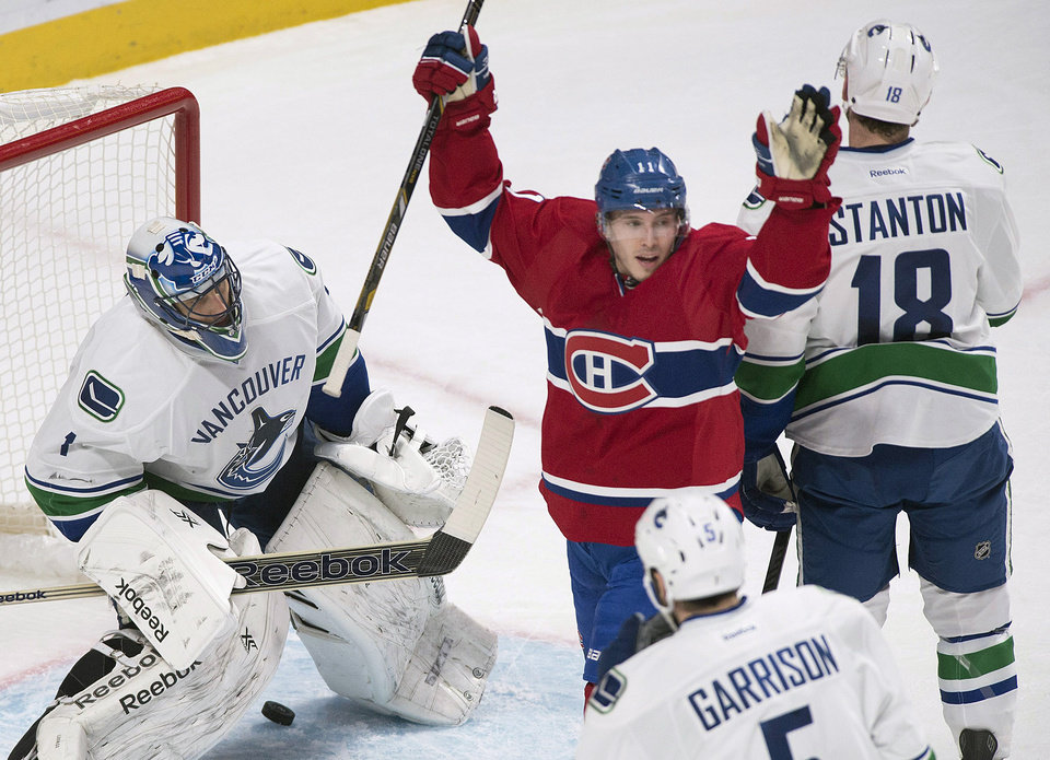 Photo - UPDATES WITH CHANGE IN CREDIT FOR GOAL, TO MAX PACIORETTY, INSTEAD OF P.K. SUBBAN - Montreal Canadiens' Brendan Gallagher, center, celebrates a goal by teammate Max Pacioretty against Vancouver Canucks goaltender Roberto Luongo, left, as Canucks' Jason Garrison and Ryan Stanton react during the first period of an NHL hockey game Thursday, Feb. 6, 2014, in Montreal. (AP Photo/The Canadian Press, Graham Hughes)