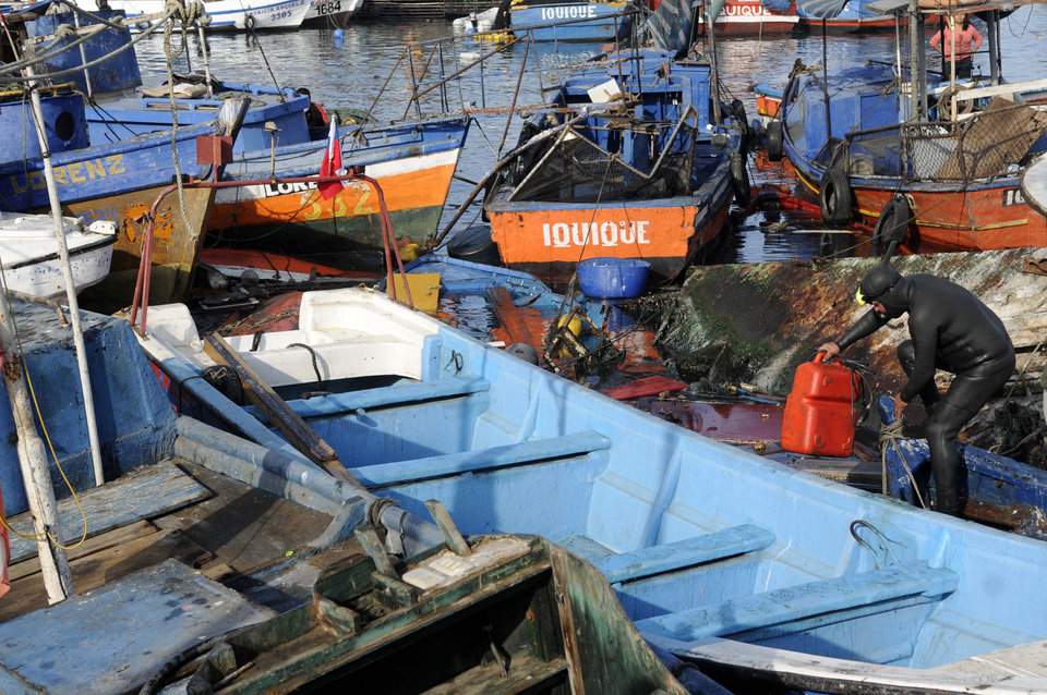 Photo - Fishing boats damaged by a small tsunami, sit in Caleta Riquelme, adjacent to the port, in the northern town of Iquique, Chile, after magnitude 8.2 earthqauke struck the northen coast of Chile, Wednesday, April 2, 2014. Authorities lifted tsunami warnings for Chile's long coastline early Wednesday. Six people were crushed to death or suffered fatal heart attacks, a remarkably low toll for such a powerful shift in the Earth's crust. (AP Photo/Cristian Viveros) NO PUBLICAR EN CHILE