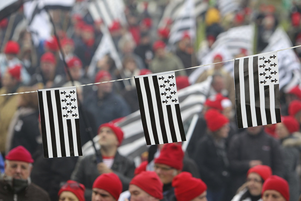 """Photo - REMOVES THE REFERENCE TO THE NUMBER OF YEARS OF THE ADMINISTRATIVE REGIONS FILE - In this Nov.30, 2013 file photo, protesters wearing red hats and flags of Brittany take part a demonstration against job losses and against the government's """"eco-tax"""", a controversial environmental tax on heavy good Is vehicles, in Carhaix, Brittany.  France's administrative regions have been part of the identity of citizens of the sprawling and diverse country. Now, merging some of them is seen as a logical way to save money on bureaucracy, and the French support it _ as long as it's someone else's region.  (AP Photo/David Vincent, FILE)"""
