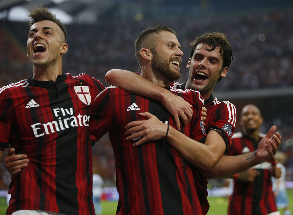 Photo - AC Milan forward Jeremy Menez, center, celebrates with teammates Stephan El Shaarawy, left, and Andrea Poli after scoring his side's third goal, during a Serie A soccer match between AC Milan and Lazio, at the San Siro stadium in Milan, Italy, Sunday, Aug. 31, 2014. (AP Photo/Luca Bruno)