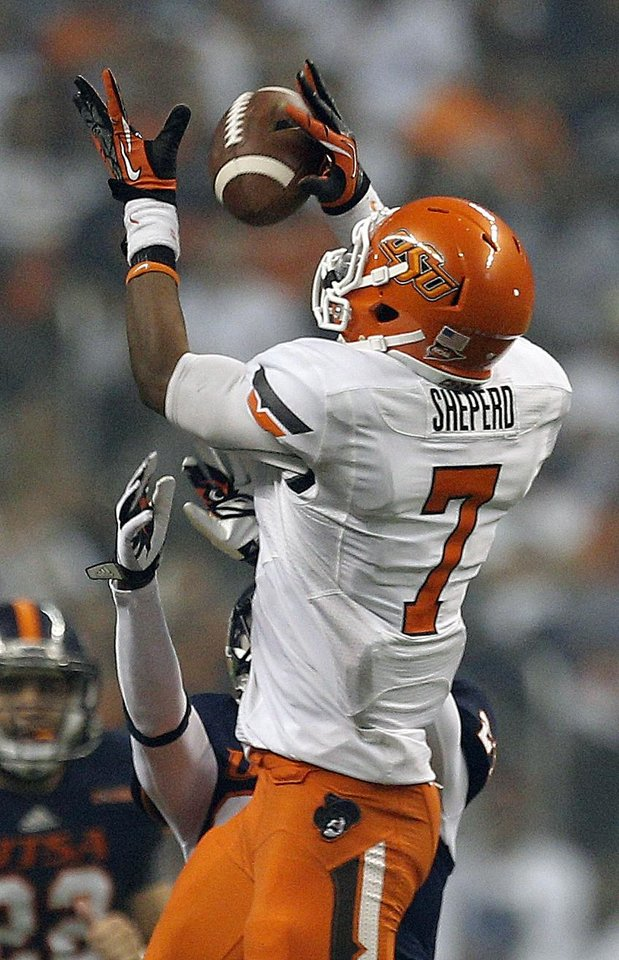 Photo - Oklahoma State's Brandon Sheperd (7) makes a catch in front of UTSA's Darrien Starling during the second half of a college football game between the University of Texas at San Antonio Roadrunners (UTSA) and the Oklahoma State University Cowboys (OSU) at the Alamodome in San Antonio, Saturday, Sept. 7, 2013.  Photo by Sarah Phipps, The Oklahoman