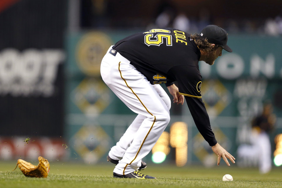 Photo - Pittsburgh Pirates starting pitcher Gerrit Cole reaches for the ball after a line drive by Toronto Blue Jays' Jose Bautista knocked his glove off in the third inning of the baseball game on Friday, May 2, 2014, in Pittsburgh. Cole made the  throw to first and Bautista was out. (AP Photo/Keith Srakocic)