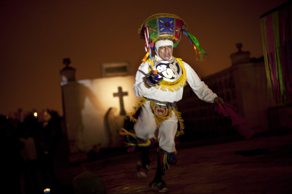 In this Dec. 6, 2012 photo, a performer dramatizes a historic event during a nighttime guided tour at the Presbitero Matias Maestro cemetery in Lima, Peru. Guides tell Peru's history through the tombs of presidents, prelates, poets, potentates and war heroes. (AP Photo/Rodrigo Abd)