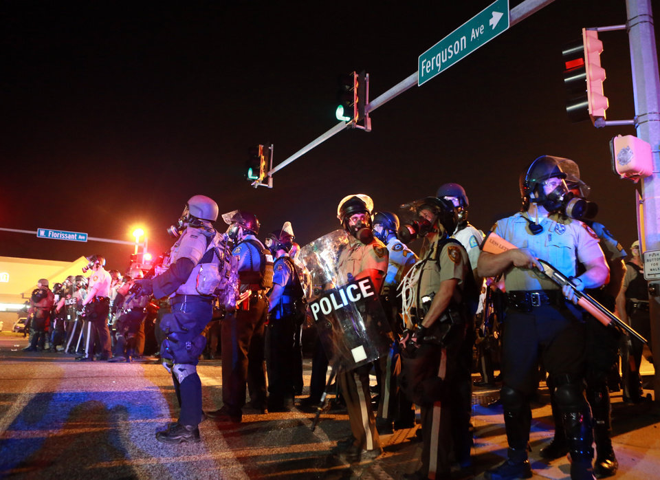 Photo - Police stand guard Monday, Aug. 18, 2014, in Ferguson, Mo. The Aug. 9 shooting of Michael Brown by a police officer has touched off rancorous protests in Ferguson, a St. Louis suburb where police have used riot gear and tear gas. (AP Photo/St. Louis Post-Dispatch, Christian Gooden)