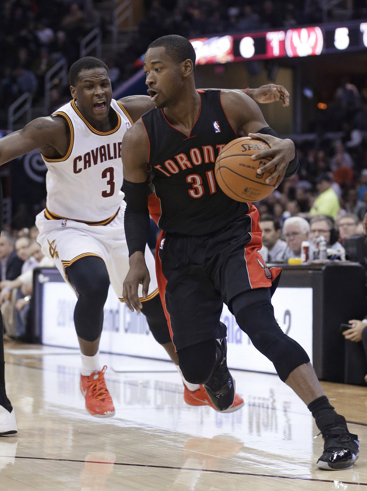 Photo - Toronto Raptors' Terrence Ross (31) drives past Cleveland Cavaliers' Dion Waiters (3) during the second quarter of an NBA basketball game Tuesday, March 25, 2014, in Cleveland. (AP Photo/Tony Dejak)