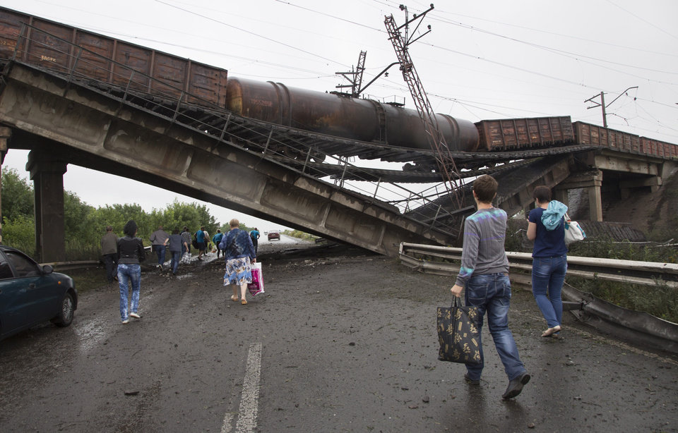 Photo - People walk under a destroyed railroad bridge over a main road leading into the east Ukraine city of Donetsk, near the village of Novobakhmutivka,  20 km North from the city of Donetsk, eastern Ukraine Monday, July 7, 2014. The bridge has been destroyed, blocking a key access route to the rebel-held city. (AP Photo/Dmitry Lovetsky)