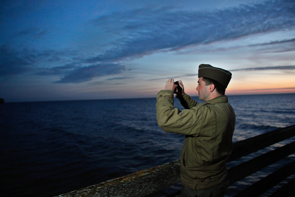Photo - A military enthusiast takes a snapshot of Omaha Beach, western France, Friday June 6, 2014. Veterans and Normandy residents are paying tribute to the thousands who gave their lives in the D-Day invasion of Nazi-occupied France 70 years ago. World leaders and dignitaries including President Barack Obama and Queen Elizabeth II will gather to honor the more than 150,000 American, British, Canadian and other Allied D-Day troops who risked and gave their lives to defeat Adolf Hitler's Third Reich.(AP Photo/Thibault Camus)