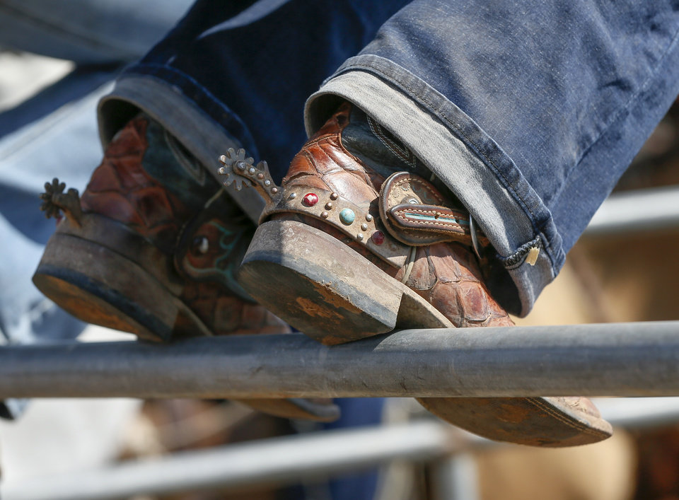 Photo - A competitor rests her boots on a fence during the International Finals Youth Rodeo at the Heart of Oklahoma Exposition Center in Shawnee, Okla., Thursday morning, July 11, 2019. [Nate Billings/The Oklahoman]