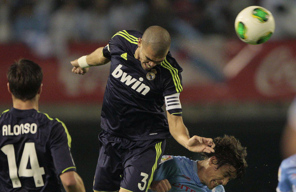 Real Madrid's Pepe from Portugal, centre jumps above Celta's  Broja Oubina to head the ball during the 1st leg of a last-16 Copa del Rey soccer match at the Balaídos stadium in Vigo, Spain, Wednesday Dec. 12, 2012. (AP Photo/Lalo R. Villar)