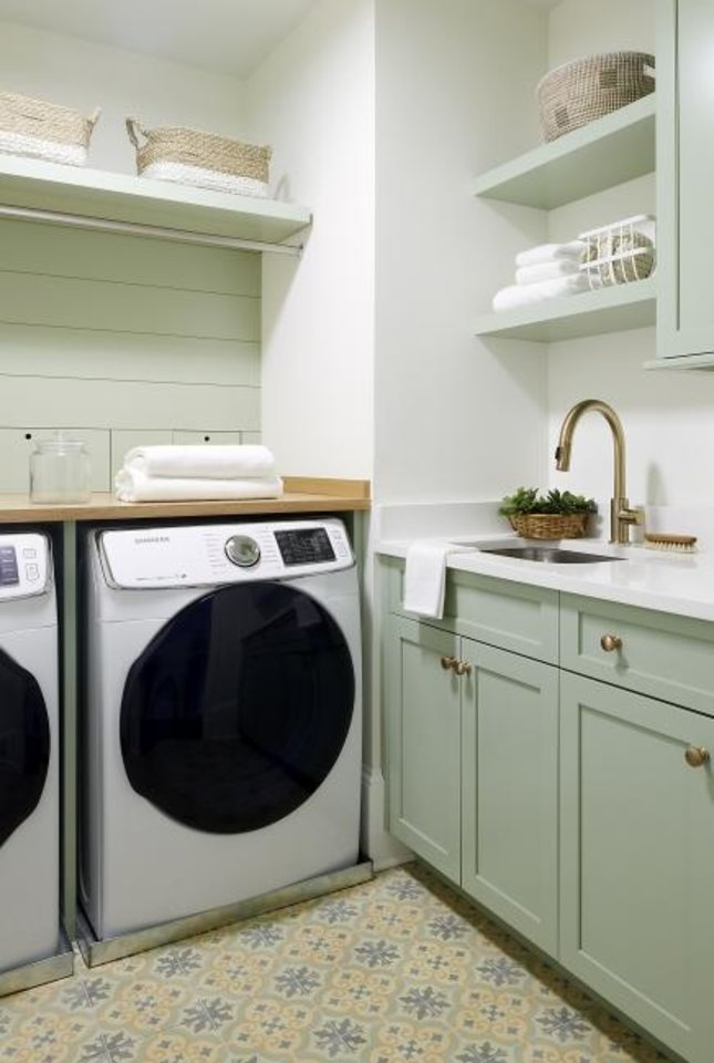 Photo -  Designer Glenna Stone put in pale green cabinets, brass accents and a Noga Trinidad patterned cement floor in this laundry room outside Philadelphia. [REBECCA McALPIN]