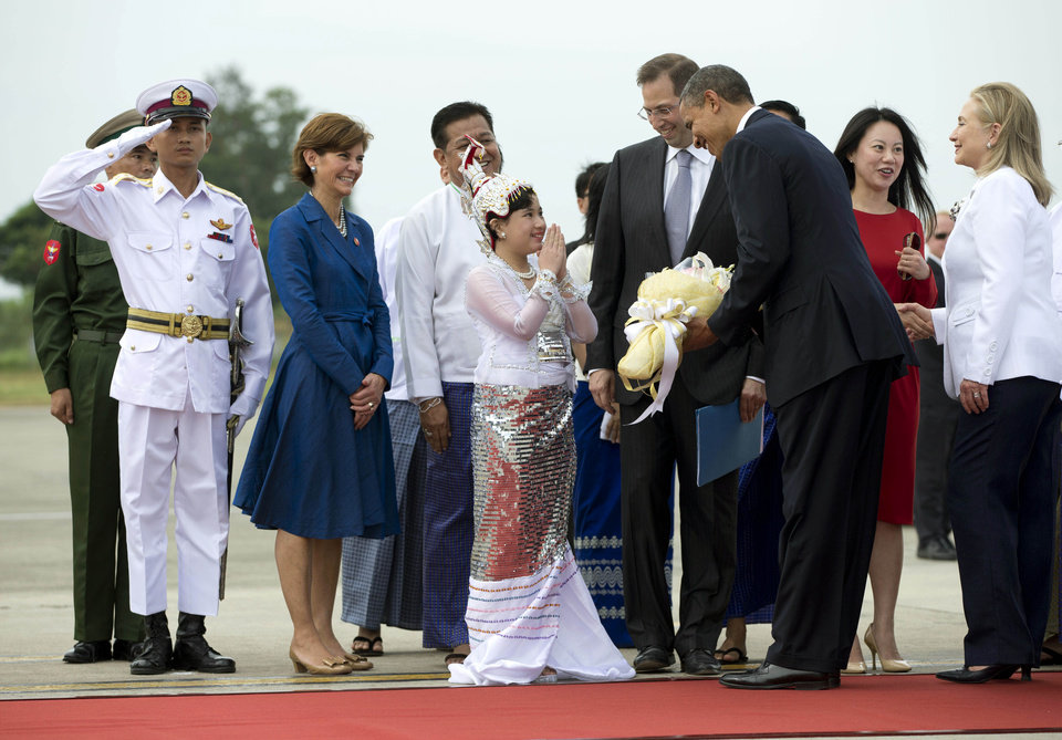 Photo -   U.S. President Barack Obama is presented with flowers as he and Secretary of State Hillary Rodham Clinton, right, arrive at Yangon International Airport in Yangon, Myanmar, on Air Force One, Monday, Nov. 19, 2012. This is the first visit to Myanmar by a sitting U.S. president. (AP Photo/Carolyn Kaster)