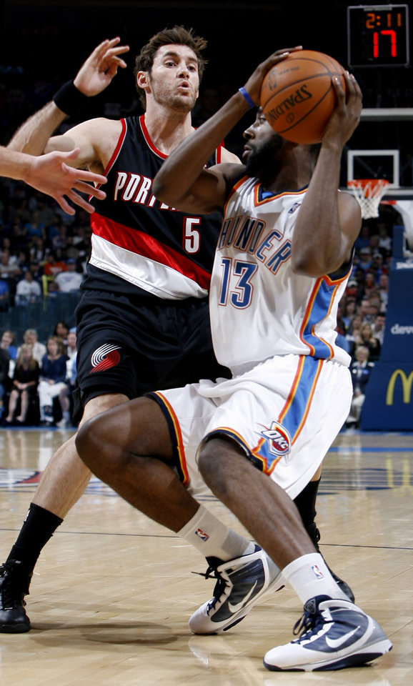 Photo - Oklahoma City's James Harden (13) looks to pass the ball as Portland's Rudy Fernandez (5) defends him during the NBA game between the Oklahoma City Thunder and the Portland Trail Blazers, Sunday, Nov. 1, 2009, at the Ford Center in Oklahoma City. Photo by Sarah Phipps, The Oklahoman