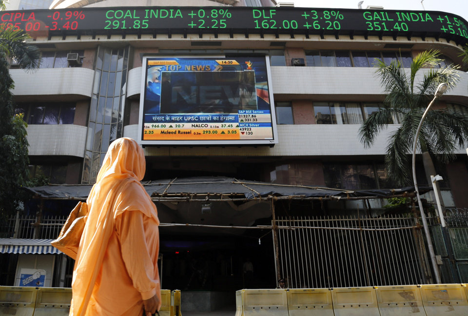 Photo - FILE - In this Dec. 9, 2013 file photo, an Indian woman looks at a screen on the facade of the Bombay Stock Exchange in Mumbai, India. From India to Indonesia, investors are finding something to like about stocks in emerging markets this year. (AP Photo/Rajanish Kakade, File)