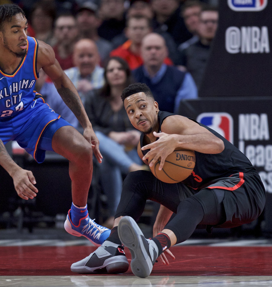 Photo - Portland Trail Blazers guard CJ McCollum, right, falls to the floor in front of Oklahoma City Thunder guard Terrance Ferguson during the first half of an NBA basketball game in Portland, Ore., Thursday, Mar. 7, 2019. (AP Photo/Craig Mitchelldyer)
