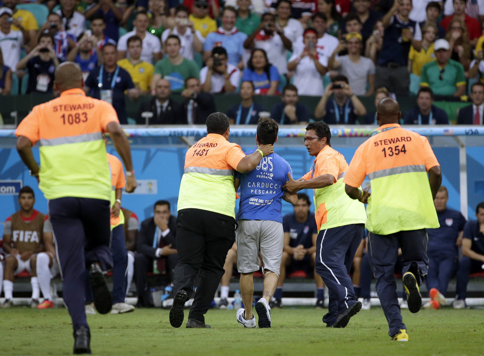 Photo - A pitch invader is taken away by security during the World Cup round of 16 soccer match between Belgium and the USA at the Arena Fonte Nova in Salvador, Brazil, Tuesday, July 1, 2014. (AP Photo/Felipe Dana)