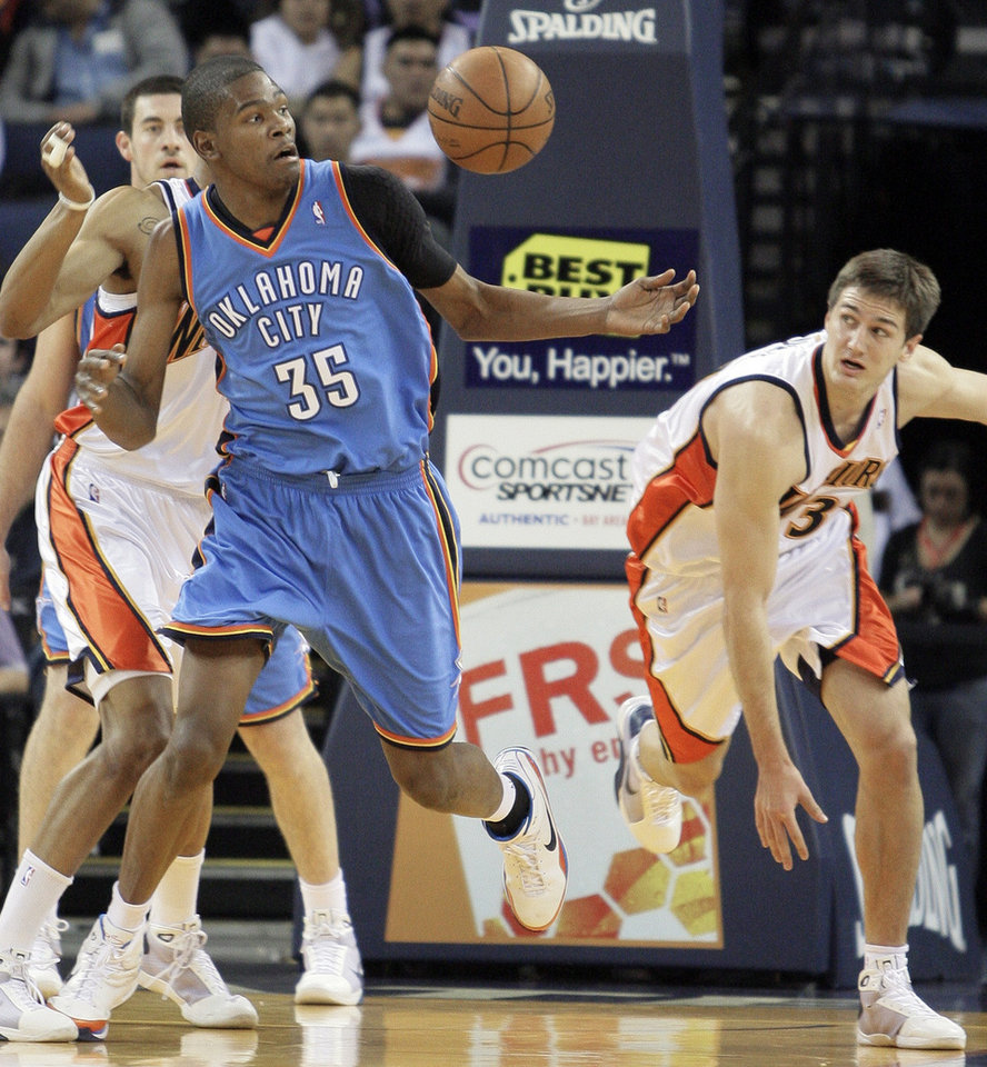 Photo - Oklahoma City Thunder guard Kevin Durant (35) and Golden State Warriors'  Rob Kurz, right, eye a loose ball during the first half of an NBA basketball game Wednesday, Jan. 21, 2009, in Oakland, Calif. (AP Photo/Ben Margot) ORG XMIT: OAS101