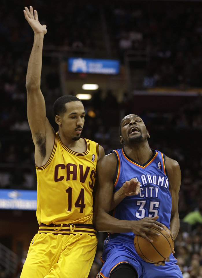 Photo - Cleveland Cavaliers' Shaun Livingston (14) fouls Oklahoma City Thunder's Kevin Durant (35) during the first quarter of an NBA basketball game on Saturday, Feb. 2, 2013, in Cleveland. (AP Photo/Tony Dejak) ORG XMIT: OHTD102