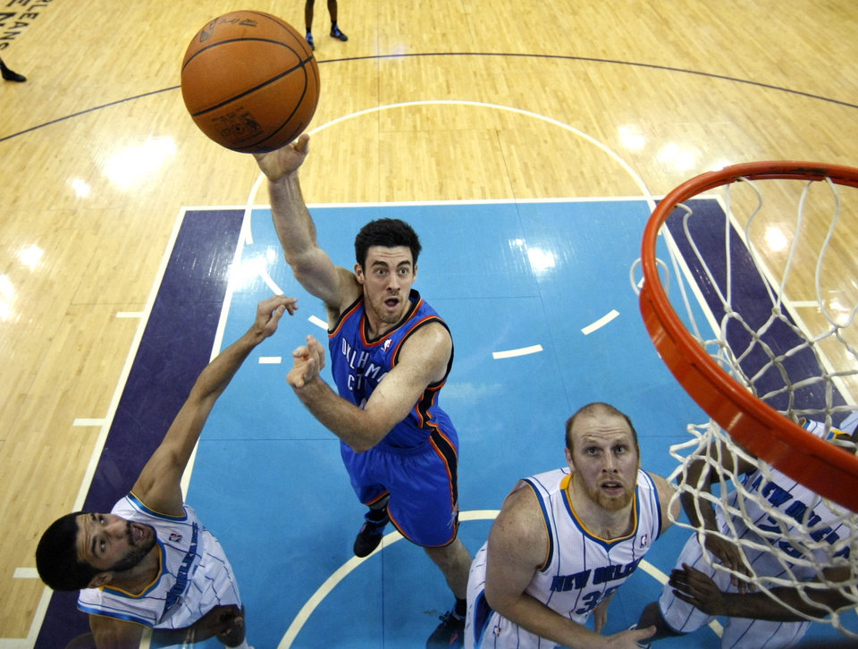 Photo - Oklahoma City Thunder power forward Nick Collison (4) shoots between New Orleans Hornets point guard Greivis Vasquez, left, and center Chris Kaman (35) in the first half of an NBA basketball game in New Orleans, Wednesday, Jan. 11, 2012. (AP Photo/Gerald Herbert)