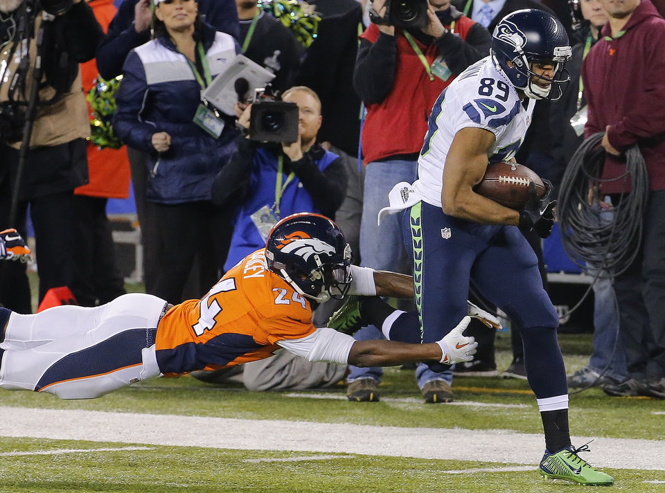 Photo - Denver Broncos cornerback Champ Bailey (24) reaches for Seattle Seahawks wide receiver Doug Baldwin (89) during the first half of the NFL Super Bowl XLVIII football game Sunday, Feb. 2, 2014, in East Rutherford, N.J. (AP Photo/Matt York)
