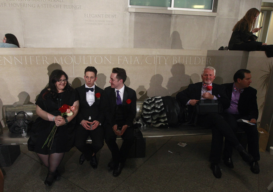 Photo - After midnight, Briceson Ducharme, second from left, sits with his partner Aaron Buck, center right, as they await their turn for a civil union vows ceremony, along with friend Errin Baumgartner, far left, who came in support, at the Webb Municipal Building in Denver, Wednesday May 1, 2013. In March 2013, the Colorado General Assembly passed SB-11, the Colorado Civil Union Act, which provides committed same-sex couples with legal protections and responsibilities. The act went into effect on May 1, 2013. (AP Photo/Brennan Linsley)