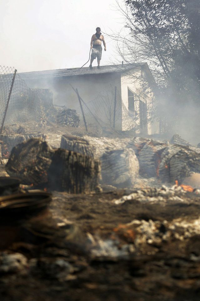 Photo - Jeff Brown waters the roof of his home as vegetation smolders during a wildfire Thursday, May 15, 2014, in Escondido, Calif. One of the nine fires burning in San Diego County suddenly flared Thursday afternoon and burned close to homes, trigging thousands of new evacuation orders. (AP Photo/Gregory Bull)