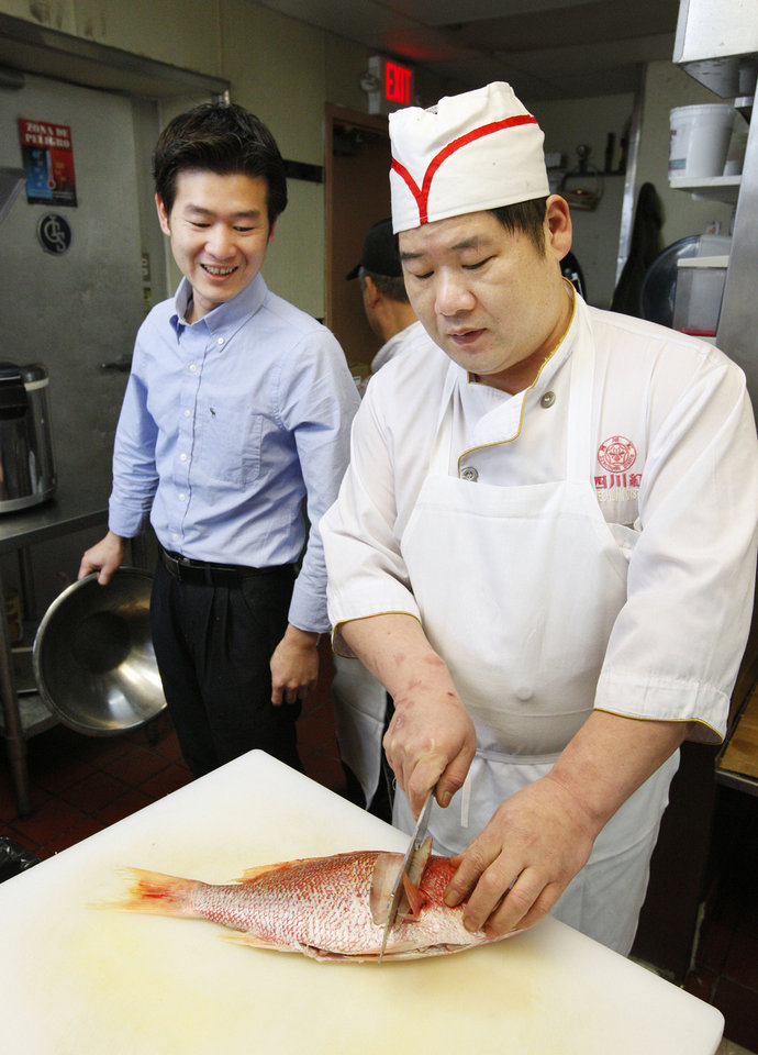 Owner Leo Chen and his brother Yuan Zhong Chen in the kitchen with a red snapper at Szechuan Bistro in Oklahoma City. <strong>PAUL B. SOUTHERLAND - THE OKLAHOMAN</strong>